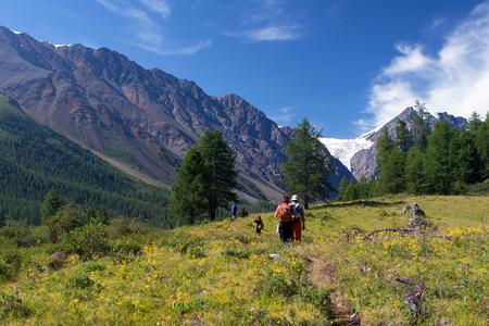 aktru: Tourists walking on the road to Aktru Glacier in the Altay Mountains, Russia. Stock Photo