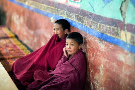 gelugpa: LADAKH, INDIA - JUNE 11, 2012: Young Tibetan Buddhist monk praying in Thiksey gompa of the Yellow Hat (Gelugpa sect). Editorial