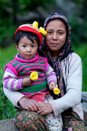 petite fille musulmane: Young smiling woman with her son poses for a photo on June 13, 2012 in Turtuk Village, Ladakh, India. Turtuk village opened to foreign tourists in 2010.