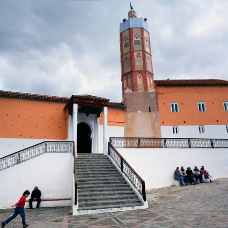noteworthy: CHEFCHAOUEN, MOROCCO - JANUARY 2, 2014: People resting on the square nearby Grand Mosque in Medina of Chefchaouen, Morocco. Noteworthy for its unusual octagonal tower, the Grande Mosque was built in the 15th century by the son of the towns founder, Ali b