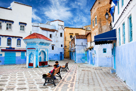 maroc: CHEFCHAOUEN, MOROCCO - JANUARY 2, 2014: Children resting at square of Chefchaouen Medina