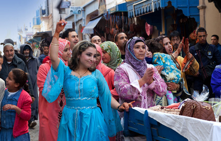 ESSAOUIRA, MOROCCO - JANUARY 15, 2014: Participants of traditional Muslim wedding ceremony dancing on the street.