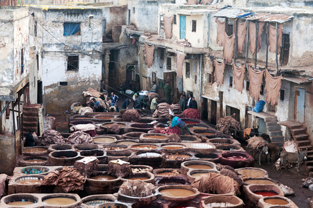 weavers: FEZ, MOROCCO - JANUARY 4, 2014: Men working hard in the tannery souk in Fez, Morocco. The tannery souk of weavers is the most visited part of the 2000 years old city.