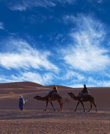 village man: ERG CHEBBI, MOROCCO - JANUARY 6, 2014: Tourists crossing in desert in Western Sahara, Morocco. Tourism is an important item in the economy of Morocco.