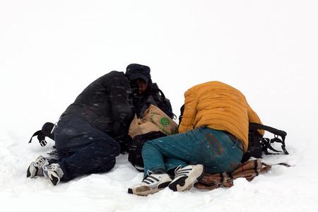 NGARI, TIBET - MAY 6, 2013: Two Tibetan pilgrims sleeping over snow during snowstorm on the trail around sacred mount Kailash in Ngari Prefecture, Tibet Autonomus Region of China. Editorial