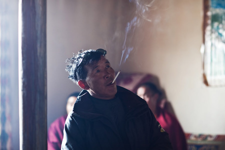 guesthouse: DARCHEN, CHINA - MAY 4, 2013: Tibetan man smoking in dinner room of monastery guesthouse in Darchen village, Tibet Autonomus Region of China Editorial
