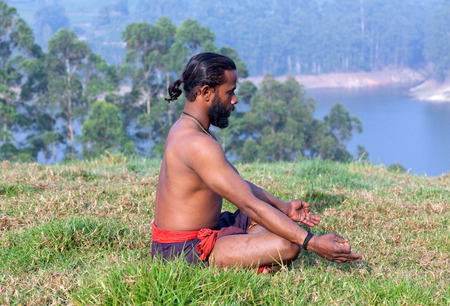 Healthy life exercise concept - sporty fit Indian man meditating in lotus yoga pose on green grass in Kerala, South India