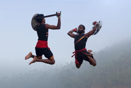 Indian fighters performing Aayudha Payattu (Weapon Combat) during Kalaripayattu Marital art demonstration in Kerala, South India Stock Photo