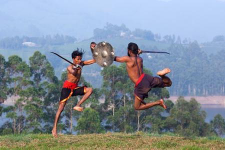 Combatientes indios realizando combate de armas durante la demostración de arte marital Kalaripayattu en Kerala, India del Sur Foto de archivo
