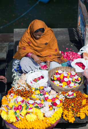 VARANASI, INDIA - JANUARY 3, 2016: Indian woman sitting on the ghats and selling pooja items for the offering - diya, orange and yellow colored marigold flowers.