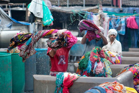 MUMBAI, INDIA - JANUARY 12, 2016: Indian workers washing clothes at Dhobi Ghat, a well know open air laundromat in downtown of Mumbai, Maharashtra State