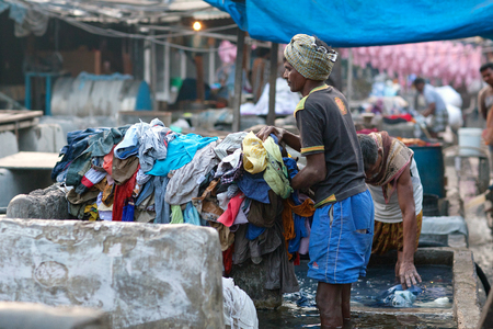 MUMBAI, INDIA - JANUARY 12, 2016: Indian workers washing clothes at Dhobi Ghat, a well know open air for clothes washing in downtown of Mumbai, Maharashtra State