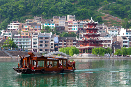 riverbank: Zhenyuan, China - May 2, 2014: Tourists floating on the boat on Wuyang River in ancient town Zhenyuan of Guizhou Province.