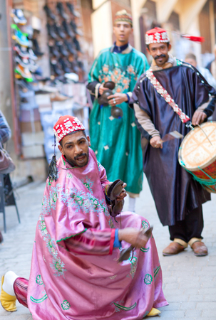 fes: FEZ, MOROCCO - JANUARY 14, 2014: Musicians playing traditional instruments in the street for tourists and shoppers in Fez Medina