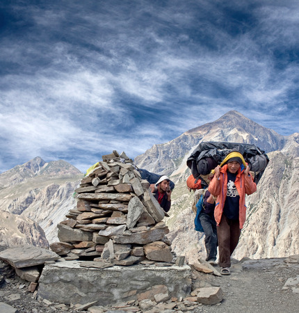 DOLPO, NEPAL - SEPTEMBER 16, 2011: Nepalese porters carrying heavy load at Sangda Pass in Shey Phoksumdo National Park, Upper Dolpo Restricted Area, Nepal, Himalayas Editorial