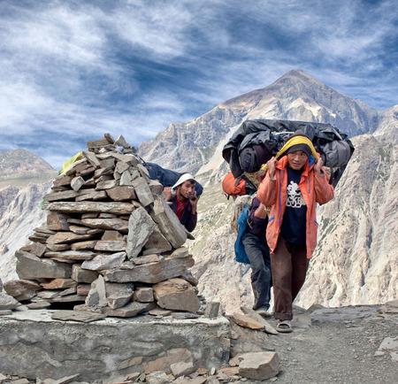 DOLPO, NEPAL - SEPTEMBER 16, 2011: Nepalese porters carrying heavy load on Sangda Pass in Shey Phoksumdo National Park
