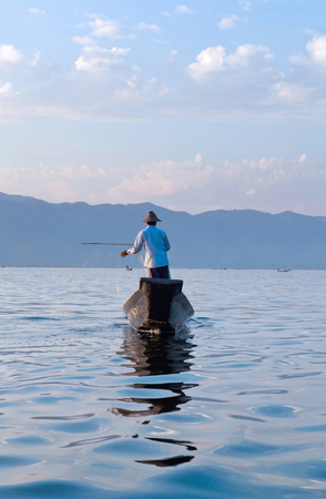 An unidentified Intha fisherman catches fish for food on Inle Lake in Shan state, Myanmar. Intha people possess the feet-rowing style and the unique fishing equipment. Stock Photo