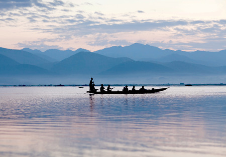 Silhouette of a traditional fishers boat at sunset on the Inle lake in Shan state of Myanmar