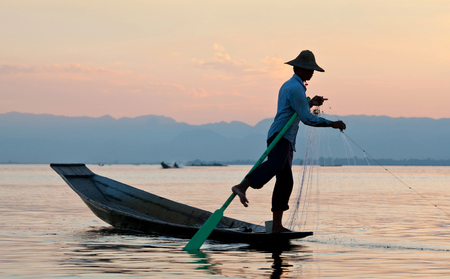 An unidentified Intha fisherman catches fish for food at sunset on Inle Lake in Shan state of Myanmar