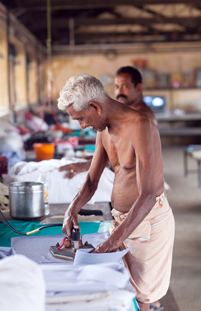 COCHI, INDIA - JANUARY 21, 2016: Indian man working hard on Dhobi Ghat in Fort Cochin, South India Editorial