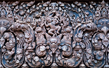 Abduction of Sita - ancient bas-relief at the facade of Banteay Srey Temple in Angkor Area, Cambodia. Banteay Srey is a 10th century Cambodian temple dedicated to the God Shiva