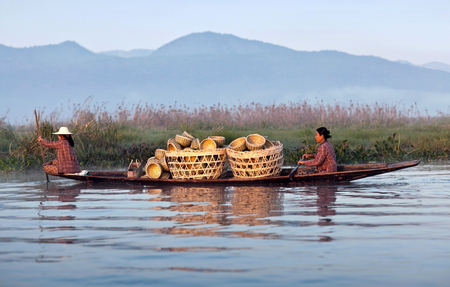 boatman: NYAUNG SHWE, MYANMAR - JANUARY 12, 2012: Intha women with manufactured goods sailing in wooden boat to weekly market on Inle Lake, Shan State Editorial