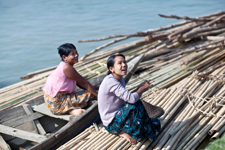 MANDALAY, MYANMAR - JANUARY 6, 2012: Smiling Burmese women traveling by wooden boat on Irrawaddy river Editorial