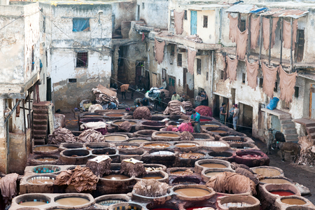 weavers: FEZ, MOROCCO - JANUARY 4, 2014: Men working hard in tanneries in Fez, Morocco. The tannery souk of weavers is the most visited part of the 2000 years old city.