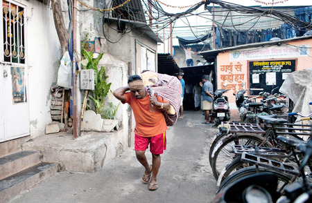 MUMBAI, INDIA - JANUARY 12, 2016: Indian porter carrying heavy load with dirty clothes to Dhobi Ghat, open air laundromat in downtown of Mumbai in Maharashtra State