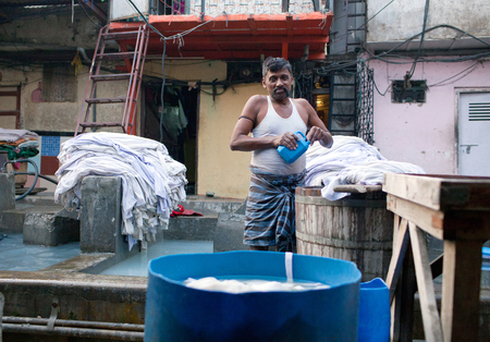 MUMBAI, INDIA - JANUARY 12, 2016: Indian workers washing clothes at Dhobi Ghat, a well know open air laundry place in downtown of Mumbai in Maharashtra State