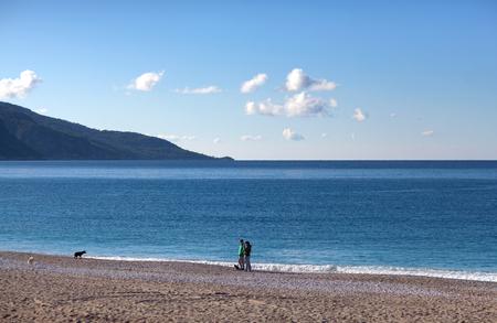 OLU DENIZ, TURKEY - November 5, 2017: Tourists walking with dogs on the Belcekiz beach Editorial
