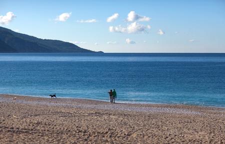 Tourists walking with dogs on the Belcekiz beach in Oludeniz, Turkey
