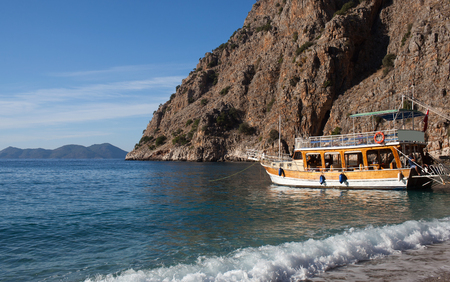 Turkish touristic boats over calm sea in beautiful lagoon in Butterfly valley, Oludeniz, Turkey