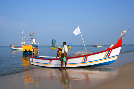 KERALA, INDIA - NOVEMBER 7, 2016: Indian fishermen catching fish for food in wooden boats in Arabian sea, South India