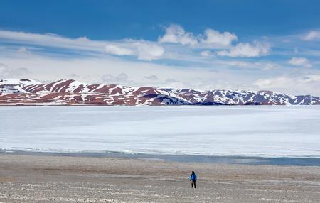 An unidentified tourist walking on shore of Rakshas Tal lake in Western Tibet, China. This lake also known as Demons Lake, Ravana Tal or Ravan Harda in Hindu Religion.