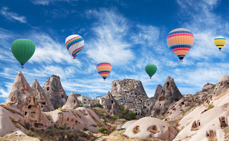 Uchisar fortress and colorful hot air balloons flying over valley in Cappadocia, Anatolia, Turkey