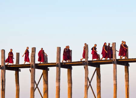 AMARAPURA, MYANMAR - JANUARY 13, 2011: Buddhists monks walking on famous U Bein teak bridge on taungthaman lake in Mandalay Division of Myanmar