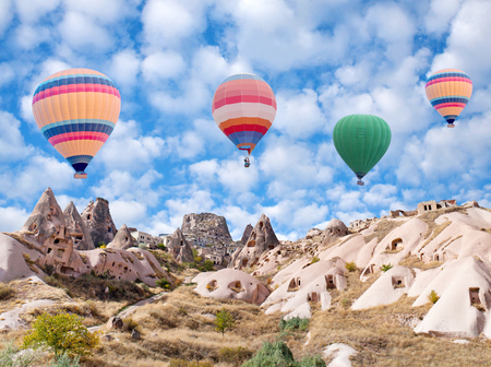 Uchhisar fortress and colorful hot air balloons flying over Pigeon valley in Cappadocia, Anatolia, Turkey 免版税图像