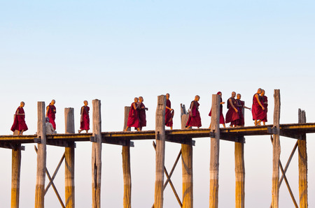 AMARAPURA, MYANMAR - JANUARY 13, 2011: Buddhist monks walking on famous U-Bein teak bridge on Taungthaman lake  in Amarapura, Mandalay Division