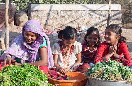 MAHARASHTRA, INDIA - JANUARY 10, 2016: Indian girls selling vegetables at local market Editorial