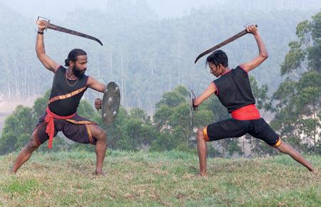 Indian fighters with sword and shield performing Aayudha Payattu (Weapon Combat) during Kalaripayattu Marital art demonstration in Kerala, South India Stock Photo