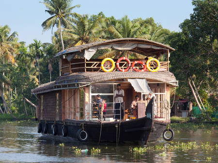 KERALA, INDIA - NOVEMBER 7, 2016: Tourists on houseboat floating in backwaters in Kerala, South India