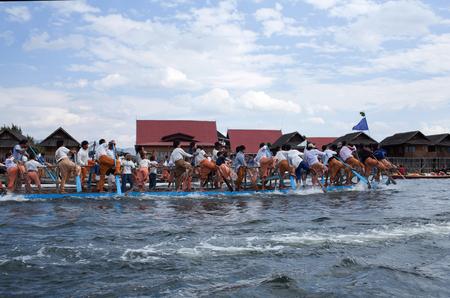 NYAUNG SHWE, MYANMAR - JANUARY 17, 2011: Team of Burmese leg rowers crossing the lake during annual Buddhist Phaung Daw U festival on Inle Lake, Shan State
