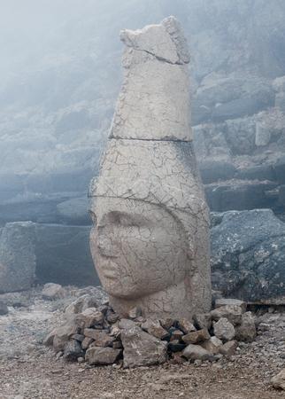Ancient ruined stone statue of God Apollo, or Mithra on the top of Nemrut mount, Anatolia, Turkey
