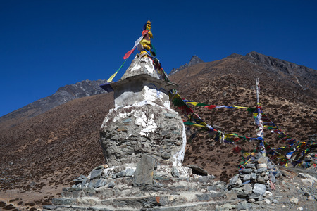 Ancient Buddhist stupa with prayer flags above Dingboche village on the way to Everest base camp, Sagarmatha National Park, Nepal Himalayas
