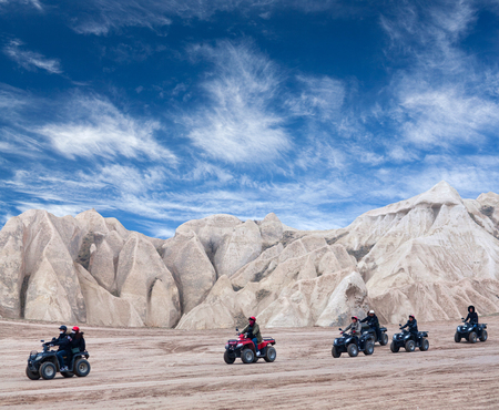 GOREME, TURKEY - JANUARY 8, 2018: Happy tourists enjoying a quad bike ride on the mountains road in countryside over Red Valley in Cappadocia, Central Anatolia