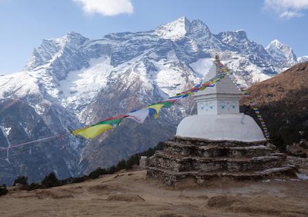 Buddhist white stupa with prayer flags above Namche Bazaar on the way to Everest base camp, Sagarmatha National Park, Nepal Himalayas