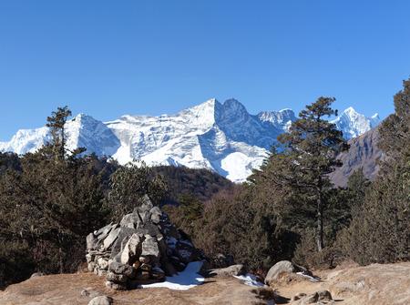 Kangtega, Thamserku and Ama Dablam mountain view and ancient mani wall on the road to Everest Base Camp in Sagarmatha National Park, Nepal Himalayas Stock Photo