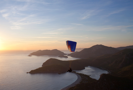 An unidentified paraglider flying at sunset over Blue lagoon in Oludeniz, Turkey Stock Photo