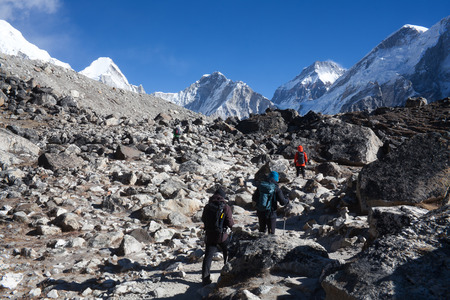 Unidentified tourists with backpacks walking on the road to Everest Base camp in Sagarmatha National Park, Nepal Himalaya